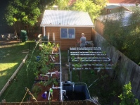 The growing area of our aquaponics system … grow beds on the left and NFT rails on the right (Garden Guru at the potting table—back of shot)